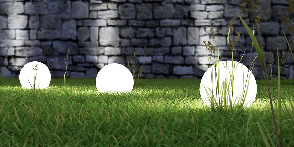 Eclairage avec des boules lumineuses posées sur le gazon près d'un mur en pierres